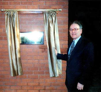 Bill Rosser unveils a plaque at the Rosser building at Sutton High School